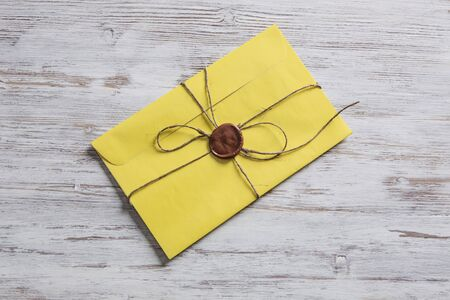 Old post concept with envelope with wax seal on wooden surface