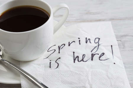 spring message: Spring is here message written on napkin and cup of coffee Stock Photo