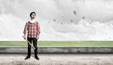 Young hipster guy with bat on asphalt road Stock Photo