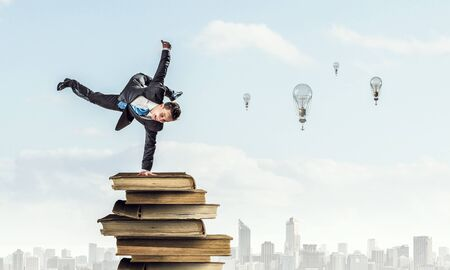 Active businessman making handstand on pile of books