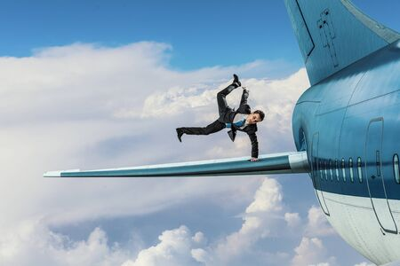 Active businessman making handstand on airplane wing