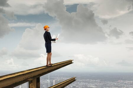 Young woman architect in hardhat standing on balk Stock Photo