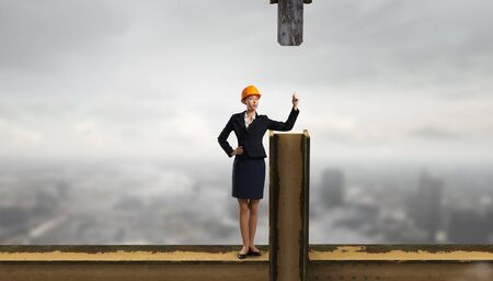 balk: Young woman architect in hardhat standing on balk Stock Photo