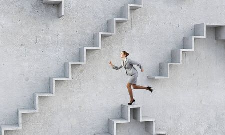reaching up: Young businesswoman reaching up staircase as symbol of growth and progress Stock Photo