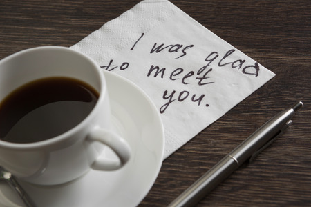 drink me: Romantic message written on napkin and cup of coffee on wooden table