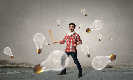 Hipster guy with baseball bat and light bulbs around Stock Photo