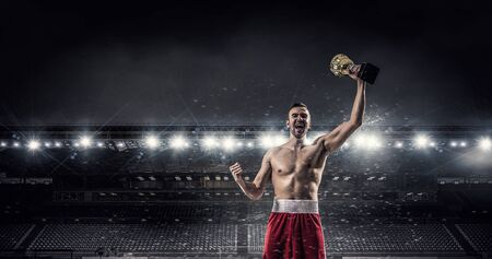 Boxer man at arena raising hand with golden cup