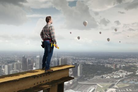 Builder man in checked shirt with tool belt on waist