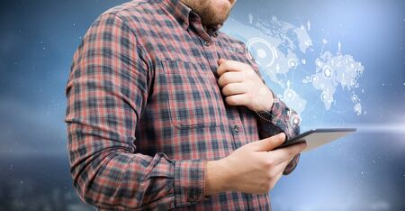 Young thoughtful man in checked shirt using tablet pc