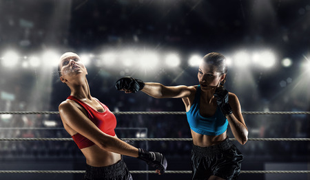 Two young pretty women boxing in ring