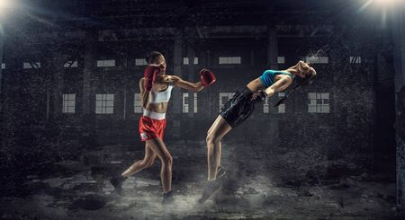 desolate: Two young pretty women boxing in desolate building. Mixed media