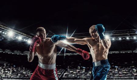 Zwei Berufsboxers, die auf Arena in den Scheinwerfern kämpfen