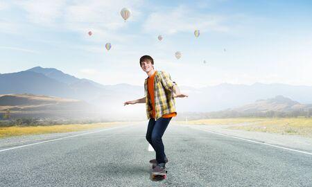 Active guy riding skateboard on asphalt road