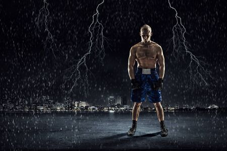 endurance: Strong boxer on dark background demonstrating power and endurance