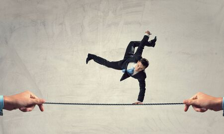 handstand: Active young businessman making handstand on rope