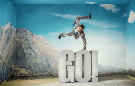 lean on hands: Active businessman making handstand on word go Stock Photo