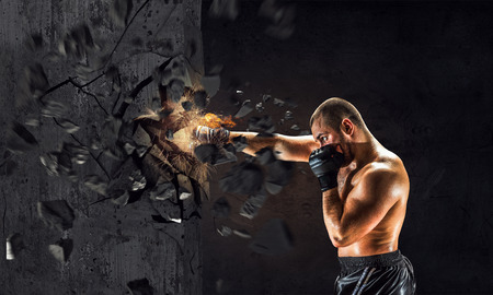 Strong boxer man in gloves breaking cement wall Stock Photo