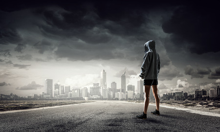 Young boxer woman standing outdoors against city landscape