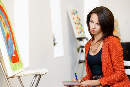 Young caucasian woman standing in an art gallery in front of painting displayed on white wall Stock Photo