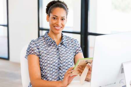 afroamerican: Portrait of beautiful smiling afro-american office worker in office looking at photograph Stock Photo