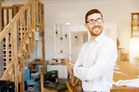 into: Young businessman standing in office and smiling into the camera