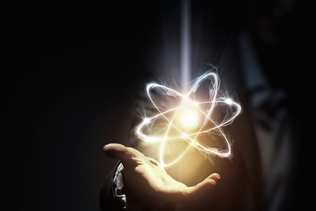 Woman scientist presenting atom research concept in palm
