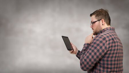 Young man in checked shirt holding tablet pc device