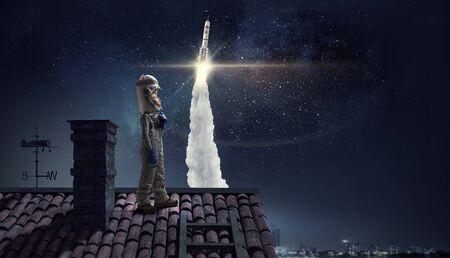 La muchacha divertida en traje espacio en tejado de la casa soñando que es astronauta Foto de archivo