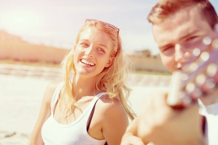 Happy romantic young couple playing guitar on beach in love Stock Photo