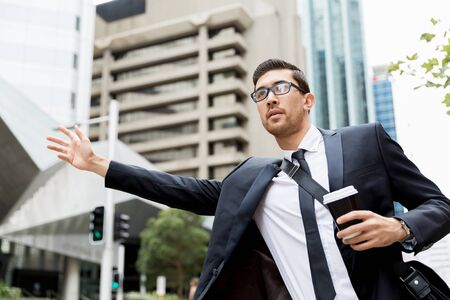 catching taxi: Young businessman wearing suit catching taxi