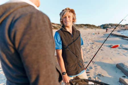 Senior man fishing with his teenage grandson at seaside