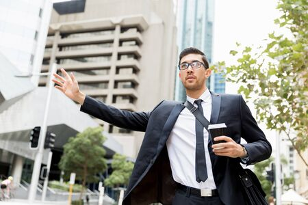 catching taxi: Young businessman in suits catching taxi