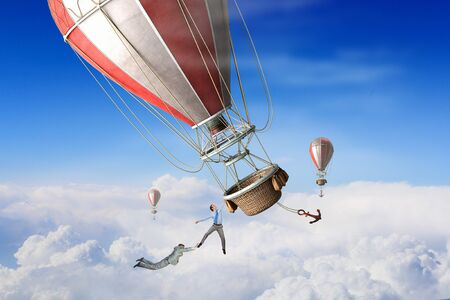 Businesspeople flying in aerostat high in sky Stock Photo