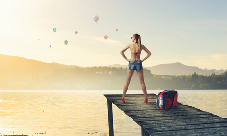 berth: Young woman tourist in shorts standing on wooden berth