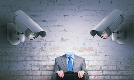 keep an eye on: Unrecognizable businessman in room standing under security camera