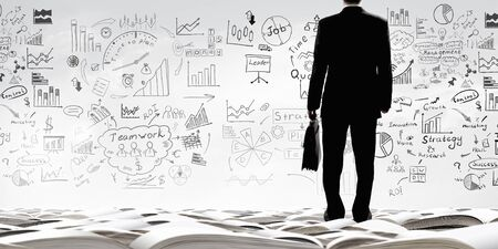business ideas: Bottom view of businessman and business ideas sketched at background Stock Photo