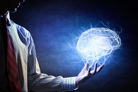 Zakenman die digitaal beeld van hersenen in palm houdt Stockfoto