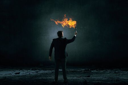 seeking solution: Young businessman in darkness holding burning torch in hand Stock Photo