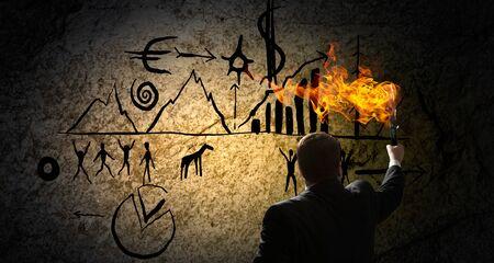pintura rupestre: Hombre de negocios joven en la oscuridad sosteniendo antorcha encendida en la mano