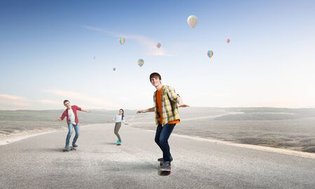 Active teenagers riding skateboard on asphalt road