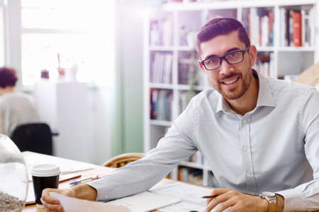 Young businessman sitting at desk and working in office