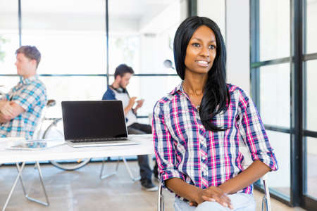 afroamerican: Portrait of beautiful smiling afro-american office worker sitting in office