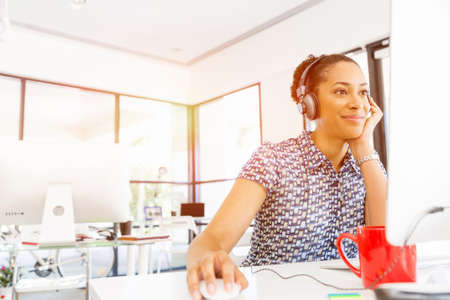 afroamerican: Portrait of beautiful smiling afro-american office worker sitting in office with headphones