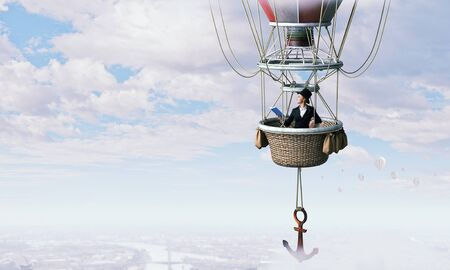 Woman in cylinder flying in aerostat high in sky