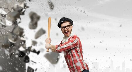 Young man in checked shirt with baseball bat