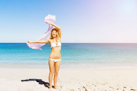 Portrait of young pretty woman in white bikini relaxing on sandy beach Stock Photo