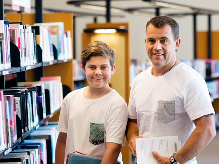 Boy and his father in library choosing books