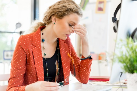Young woman in casual clothes in an office tired