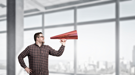 amplify: Guy in checked shirt make announcement in red paper trumpet. Mixed media Stock Photo