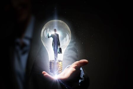 holding close: Close view of businesswoman holding in palm glass light bulb